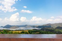 Empty wood table top on Nature scene of Srinagarind Dam with cloudy sky at kanchanaburi ,Thailand royalty free stock image