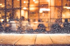 Empty wood table top with snowfall and bokeh cafe restaurant. In night winter background.For holiday,christmas day and new year concept Stock Photography