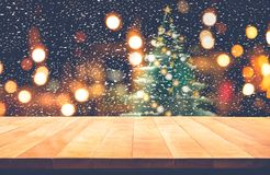 Empty wood table top with snowfall and cafe restaurant in night Stock Photography