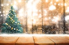 Empty wood table top with snowfall and cafe restaurant in night Royalty Free Stock Image