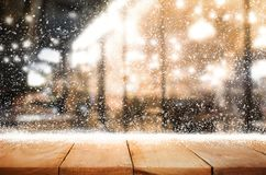 Wood table top with snowfall of winter season background.christmas. Empty wood table top with snowfall and cafe restaurant in night winter background.For holiday stock images