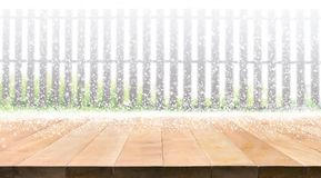 Empty wood table top with snowfall of winter season on fence Stock Image