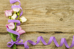 Empty wooden background with colorful flowers and purple ribbon. Empty wooden postcard with colorful flowers and purple ribbon royalty free stock photo