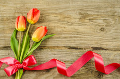 Empty wooden background with colorful flowers and red ribbon Royalty Free Stock Photos