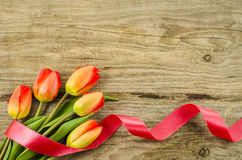 Empty wooden background with colorful flowers and red ribbon Stock Image