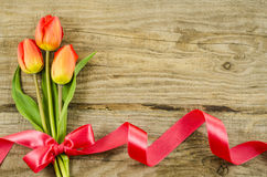 Empty wooden background with colorful flowers and red ribbon Stock Photography