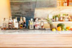 Modern hotel lounge and bar with the shelf of alcoholic drinks. Empty wooden bar counter with defocused background and bottles of Modern hotel lounge and bar Royalty Free Stock Image