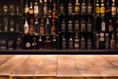 Empty wooden bar counter with defocused background and bottles of restaurant. Bar or cafeteria background royalty free stock photography