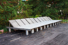 Empty wooden beach beds, arranged in a row Stock Images