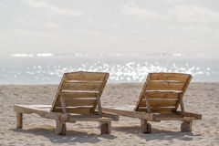 Empty wooden beach chairs on the tropical beach, vacation. Trave Royalty Free Stock Photo