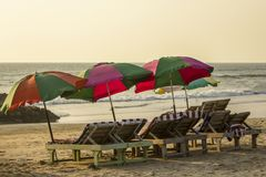 Empty wooden beach loungers with striped mattresses under bright large sun umbrellas on the sand against the background of the royalty free stock image