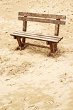 Empty wooden bench on the beach in cloudy weather Stock Photography