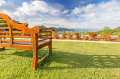 Empty wooden bench with a beautiful view of sea, sky and hills. Empty wooden bench with a beautiful view of sea, sky, clouds and hills Royalty Free Stock Photos