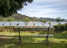 Empty wooden bench in front of a beautiful estuary. Galician landscape of the Betanzos estuary. Pazo de Mariñán stock photos
