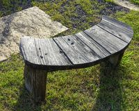 Empty wooden bench on the grass stock image