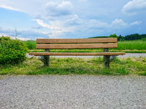 Empty wooden bench on green meadows Stock Images