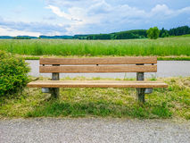 Empty wooden bench on green meadows Stock Photo