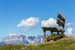 Empty wooden bench with idyllic Alps mountains landscape, low angle view, sunny summer. Day royalty free stock images