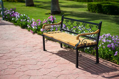 Empty wooden bench near green grass, beautiful flowers in park. Empty wooden bench on pavers road near green grass and summer or spring beautiful flowers in park Stock Photos