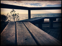 Empty wooden bench on ocean shore. At sunset closeup. Vintage retro look and feel Royalty Free Stock Photography