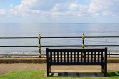 Empty wooden Bench overlooking Beach Royalty Free Stock Image
