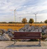 Empty wooden bench at park with beautiful background and wind turbine. For green alternative energy Stock Photography