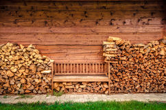 Empty wooden bench with pile of firewood. Detail of empty wooden bench with pile of firewood Royalty Free Stock Images