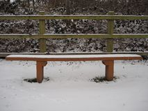 Empty wooden bench seat perfectly covered with white snow. In the winter Stock Photography