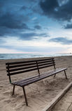 Empty wooden bench stands on sandy beach Royalty Free Stock Photography