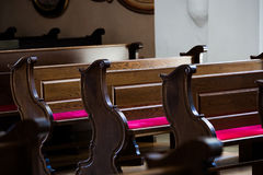 Empty wooden benches in  Catholic Church. Empty wooden benches in old  Catholic Church Royalty Free Stock Photos