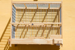 Empty wooden birdcage hanging on wall Royalty Free Stock Images