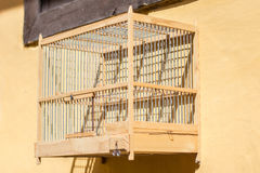 Empty wooden birdcage hanging on wall Royalty Free Stock Photos