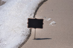 Empty wooden black sign on the beach Royalty Free Stock Photo