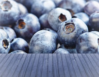 Empty wooden,blue table with fresh blueberries in background, ready for your product display montage. Royalty Free Stock Photography