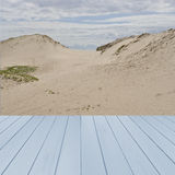 Empty wooden,blue table ready for your product display montage with dunes of sand in background, UK Royalty Free Stock Photography
