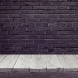 Empty wooden board background over black brick wall Royalty Free Stock Images