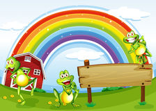 An empty wooden board with frogs and a rainbow in the sky Royalty Free Stock Photo