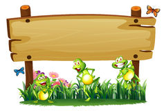 An empty wooden board at the garden with playful frogs Royalty Free Stock Photos