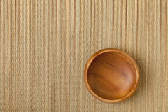 Empty wooden bowl on mat Royalty Free Stock Images