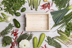 Empty wooden box on table with veggies. Empty wooden box is lying on a wooden table surrounded by different kinds of vegetables. Mock up Royalty Free Stock Image