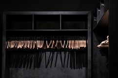 Empty wooden clothes hangers in empty black cloakroom, casting deep shadows. Photographed in London UK royalty free stock photography