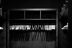 Empty wooden clothes hangers in empty black cloakroom, casting deep shadows. Photographed in monochrome stock images