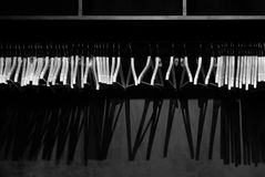 Empty wooden clothes hangers in empty black cloakroom, casting deep shadows. Photographed in monochrome stock photo