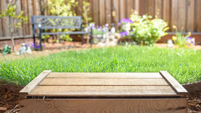 Empty wooden crate with blurred backyard on background Royalty Free Stock Photo
