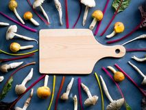 Empty wooden cutting board in center with rainbow swiss chard ve. Empty wooden cutting board in center with organic rainbow swiss chard vegetable and mushroom Stock Photos