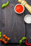 Empty wooden cutting board with frame made of ripe red cherry tomatoes and basil leaves stock images
