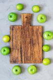 An empty wooden cutting board on a gray concrete background is surrounded by green apples and lime. An empty wooden cutting board on a gray concrete background Royalty Free Stock Images