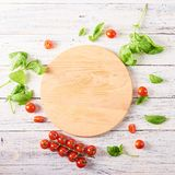 Empty wooden cutting board with tomatoes and basil stock image