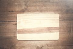 Empty wooden cutting board on a wood background. Royalty Free Stock Photos