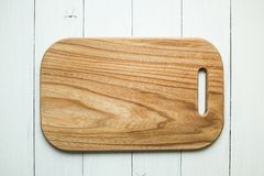 An empty wooden cutting board with a wood texture on a white table background. Top view stock photos
